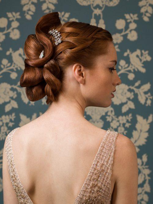 Associé à une chevelure cuivrée, le cannage et les bijoux de cheveux subliment ce chignon de mariée.
